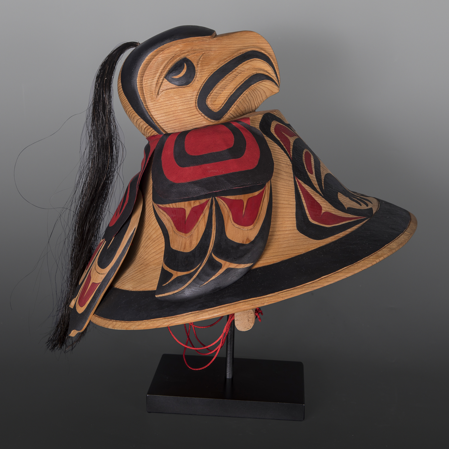 """Eagle Helmet Carol Young Bagshaw Haida Red cedar, leather, cord, horsehair, paint, custom stand 16"""" x 15"""" x 12"""" (16"""" tall with stand) $6000"""