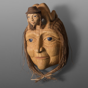 "Haida Woman Portrait Mask Carol Young Bagshaw Haida Alder, red cedar, cedar bark, paint 15"" x 10"" x 7"""